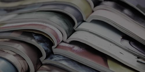A pile of open magazines, layered on top of each other