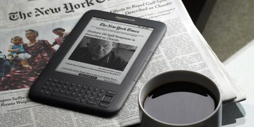 An e-reader on a newspaper with a mug of coffee in the foreground
